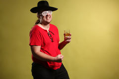 Crazy rock and rollerer with a big black hat, party glasses and a glass of whiskey in front of a cheetah skin background Stock Image