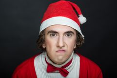 Crazy santa claus. Handsome man Santa Claus showing emotions on his face, traditional red and white hat, bow tie. actor, mime, clown. Creative idea for Christmas royalty free stock image