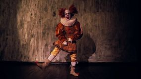 Crazy scary clown dancing against a dark red wall in darkened room. Terrible clown with colorful makeup in a festive costume. Shooting in slow motion stock video footage