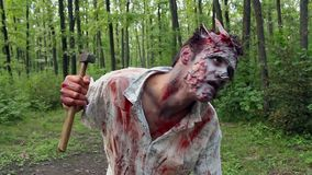 Crazy scary zombie standing in the woods and looking for the victim. He is holding a hammer stock video footage