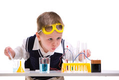 Crazy scientist. Young boy performing experiments with battery and small lamp Stock Photo