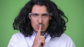 Crazy scientist with finger on lips. Studio shot of crazy scientist wearing protective glasses against chroma key with green background stock footage