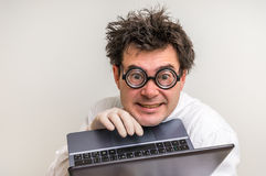 Crazy scientist with laptop working in his laboratory. Crazy scientist in glasses with laptop working in his laboratory royalty free stock photos