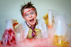 Crazy scientist performing experiments in lab. Crazy scientist. Young boy performing experiments royalty free stock photo