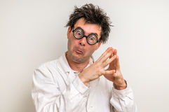 Crazy scientist thinking about his experiment. Crazy scientist with glasses thinking about his experiment Stock Image