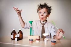 Crazy scientist. Young boy performing experiments Stock Image