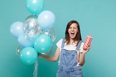 Crazy screaming young woman blinking, holding plastic cup of cola or soda celebrating with colorful air balloons. Isolated on blue turquoise background stock photo