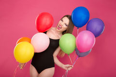 Crazy screaming young woman pozing with colorful balloons. Crazy freaky bizarre screaming young woman in black leotard pozing with colorful balloons on pink stock photography