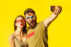 Crazy selfie. Beautiful friends macking selfie on yellow background. Studio shot stock image