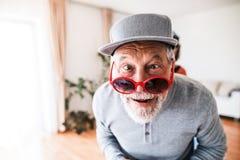 Senior man having fun at home. Crazy senior man having fun at home royalty free stock photography