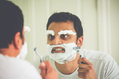 Crazy shaving. Closeup portrait, overzealous mentally deranged, mad as a hatter, young man at the end of his rope, attempting to shave his face eyebrows and face Royalty Free Stock Image
