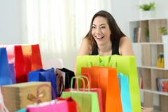 Crazy shopper looking at several shopping bags. Crazy shopaholic shopper looking at several colorful shopping bags at home Stock Image