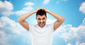 Crazy shouting man in t-shirt over blue sky Royalty Free Stock Images