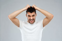 Crazy shouting man in t-shirt over gray background Royalty Free Stock Photo