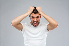 Crazy shouting man in t-shirt over gray background Royalty Free Stock Photos