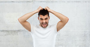 Crazy shouting man in t-shirt over gray background Stock Photography