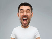 Crazy shouting man in t-shirt over gray background. Emotions, stress, madness and people concept - crazy shouting man in white t-shirt over gray background ( Stock Image