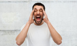 Crazy shouting man in t-shirt over gray wall Royalty Free Stock Images