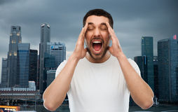 Crazy shouting man in t-shirt over singapore city Royalty Free Stock Photo