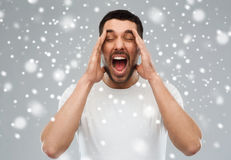 Crazy shouting man in t-shirt over snow background. Emotions, stress, winter, christmas and people concept - crazy shouting man in t-shirt over snow on gray Stock Image