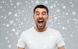 Crazy shouting man in t-shirt over snow background. Emotions, stress, winter, christmas and people concept - crazy shouting man in t-shirt over snow on gray Royalty Free Stock Photos