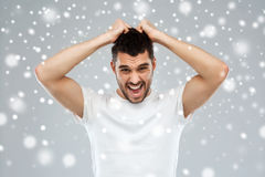 Crazy shouting man in t-shirt over snow background. Emotions, stress, winter, christmas and people concept - crazy shouting man rending ones hair in t-shirt over Royalty Free Stock Photo