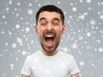 Crazy shouting man in t-shirt over snow background. Emotions, stress, winter, christmas and people concept - crazy shouting man in white t-shirt over snow on Stock Photography