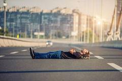 Crazy skateboarder lying down at the middle of a highway bridge Stock Photography