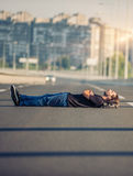 Crazy skateboarder lying down at the middle of a highway bridge Royalty Free Stock Images