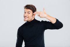 Crazy smiling man with fingers to temple like a gun Stock Images