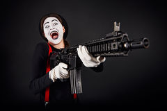 Crazy smiling mime with gun Royalty Free Stock Photography