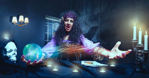 Crazy sorceress practising witchcraft. Angry sorceress working with crystal ball Royalty Free Stock Photo