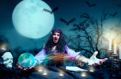 Crazy sorceress practising witchcraft. Angry sorceress working with crystal ball Stock Image