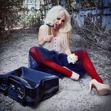 Crazy strange freak girl crashing money box by hammer. Portrait of beautiful odd woman in corset, tights and tutu skirt in forsake. Crazy strange freak girl royalty free stock photos
