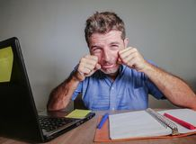 Crazy stressed and overwhelmed man working messy at office desk desperate with laptop computer doing crying hands gesture frustrat. Ed in business and work royalty free stock photography