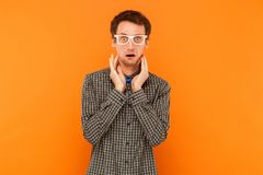 Crazy student looking at camera with shocked face. Indoor, orange background Stock Photos