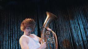 Crazy tattooed man in tank top and big fur hat perform with brass tube on scene. Crazy tattooed man in tank top and big fur hat perform with brass tube on the stock footage