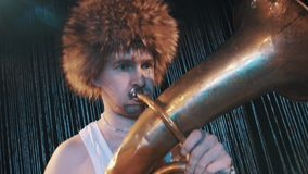Crazy tattooed man in tank top and big fur hat playing brass tube on scene. Crazy tattooed man in tank top and big fur hat playing with brass tube on the scene stock video footage