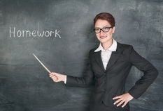 Crazy teacher with pointer. And phrase Homework on blackboard chalkboard Stock Images
