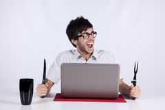 Crazy about technology. Young men at dinner table eating technology with a funny face expression Stock Photos