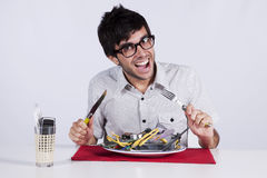 Crazy about technology. Crazy young man eating technology at his dinner plate royalty free stock photos
