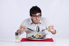 Crazy about technology. Crazy young man eating technology at his dinner plate Royalty Free Stock Photography