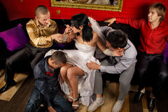 Crazy wedding. Party in night club. Friends of groom make a drunkard of bride Stock Images