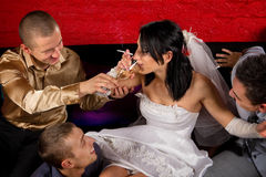 Crazy wedding. Party in night club. Friends of groom make a drunkard of bride Royalty Free Stock Photography