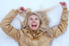 Crazy Winter girl is lying on snow Stock Image