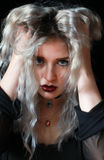 Crazy woman. Beautiful young woman with hands in hair looking straight to camera with a angry expression Royalty Free Stock Photography