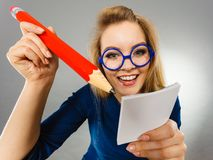 Crazy woman holds big pencil in hand. Positive crazy woman blonde student girl or female teacher, business coach holding huge red pencil and note paper, planning Stock Image