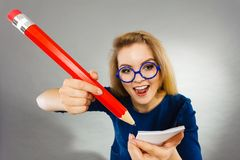 Crazy woman holds big pencil in hand Stock Photo