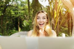 Crazy woman with laptop looking at camera, sunshine green palms in Thailand Phuket while travel. Crazy happy woman hold laptop and look at camera, background of Royalty Free Stock Photography