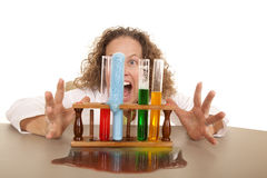 Crazy woman scientist with test tubes behind. A crazy woman scientist with some test tubes full of colored liquid Stock Photo
